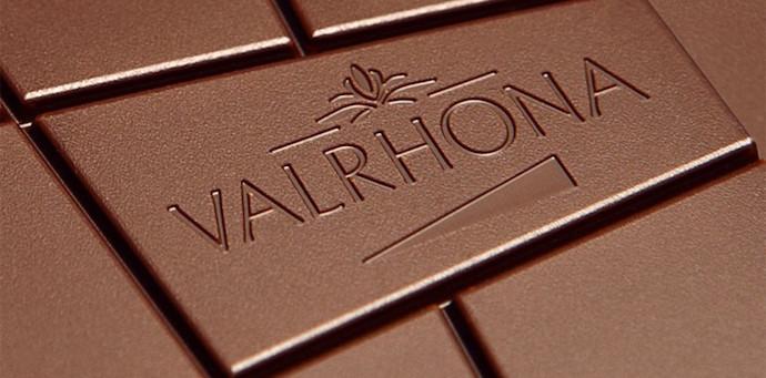 Tableta de chocolate de cerca con el logo de Valrhona marcado sobre el mismo. Chocolates Creative Signatures